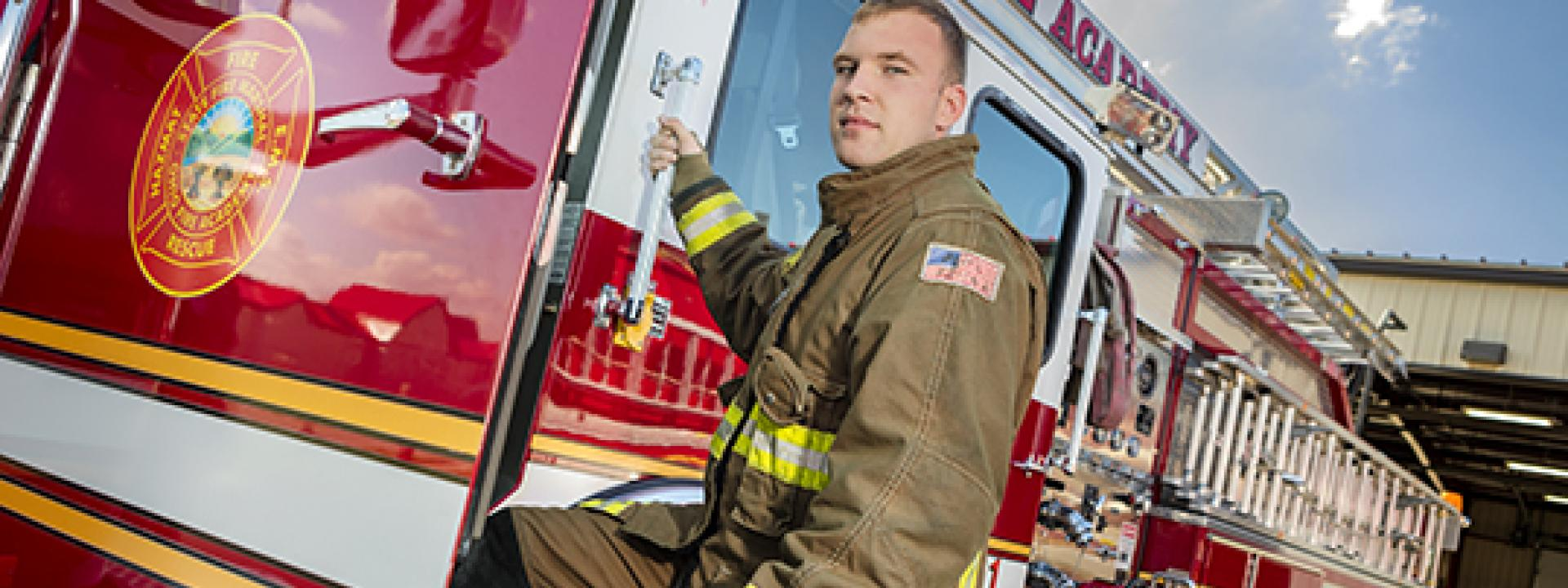 Picture of a fire fighter standing in front of a fire truck