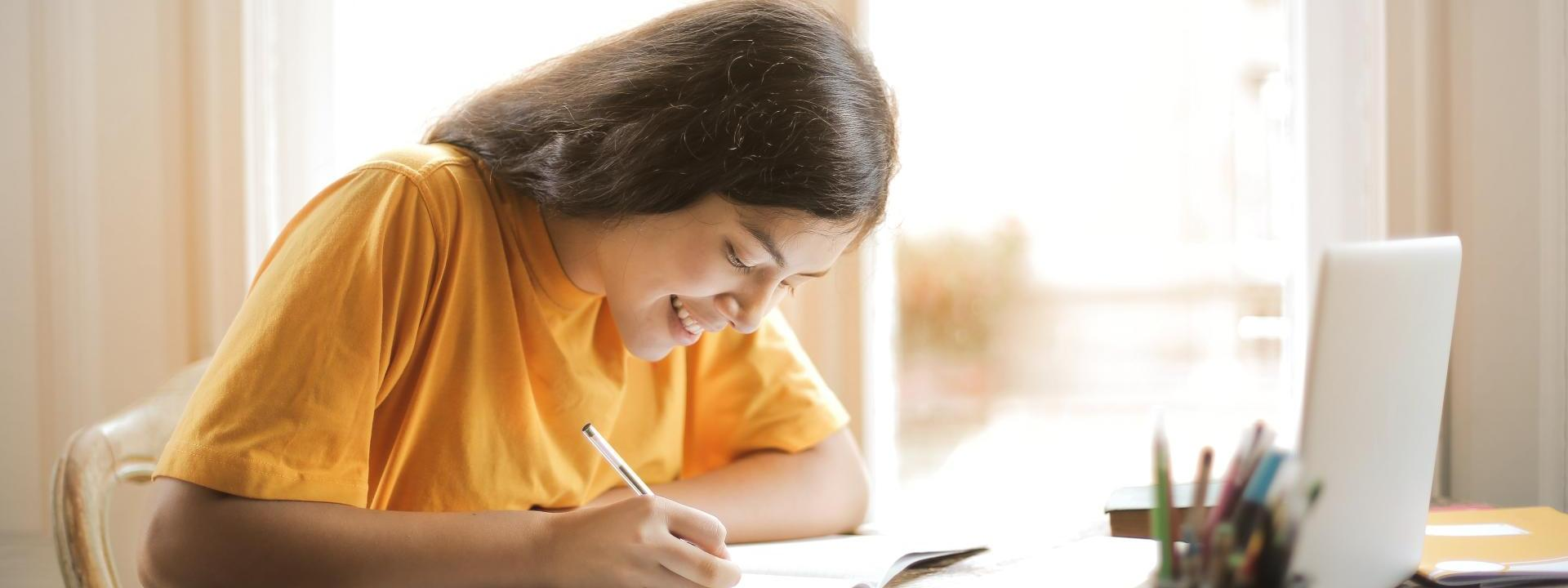 Student sitting at computer filling out paperwork