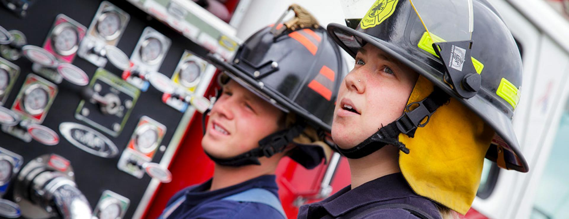 two Fire students standing at truck