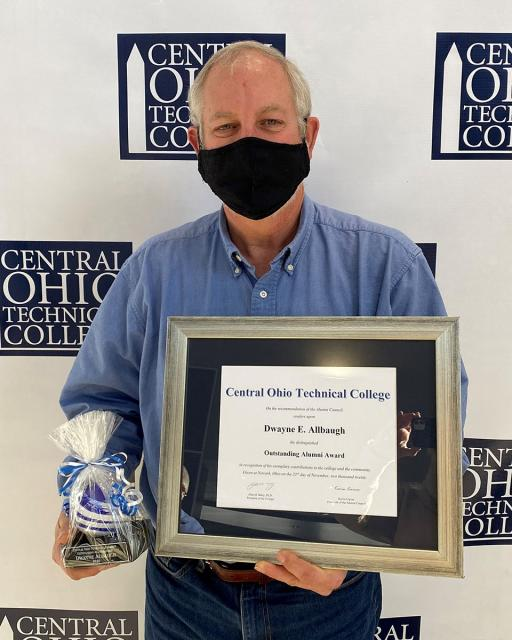 older white male wearing mask holding award in front of camera