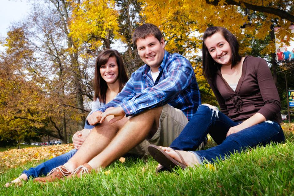 3 students sitting in grass