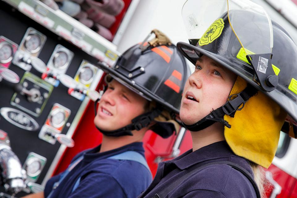 Two fire science technology students in firefighter gear next to a fire truck.