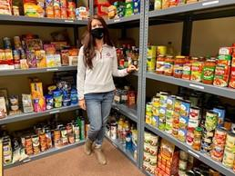 Woman standing near shelves of food with mask on smiling at camera