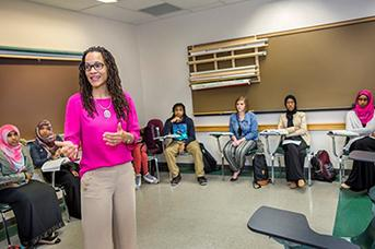 Female African-American Professor smiling in front of class
